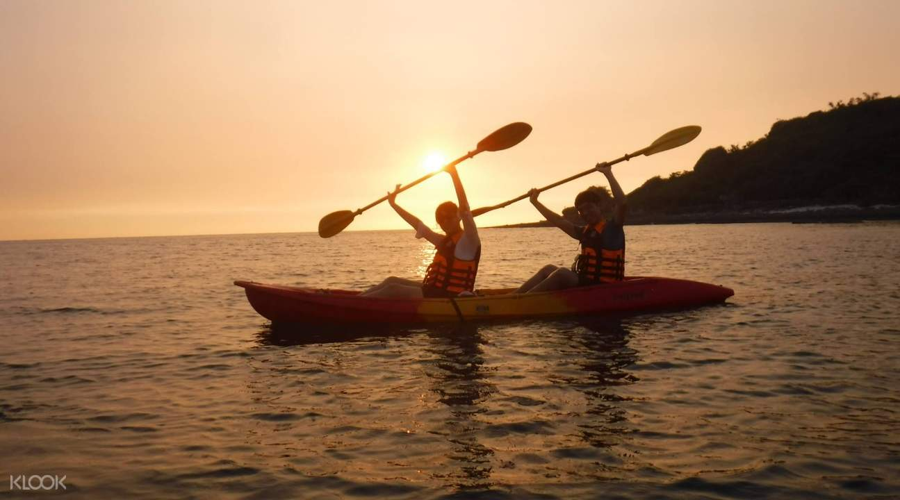 two people kayaking during the sunset